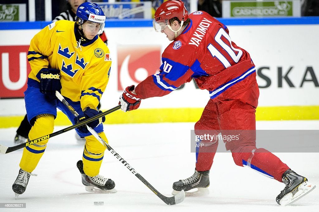 Sweden's Christian Djoos (L) and Russia's Bogdan Yakimov vie during the World Junior Hockey Championships semifinal between Sweden and Russia at Malmo Arena in Malmo, Sweden on January 4, 2014.