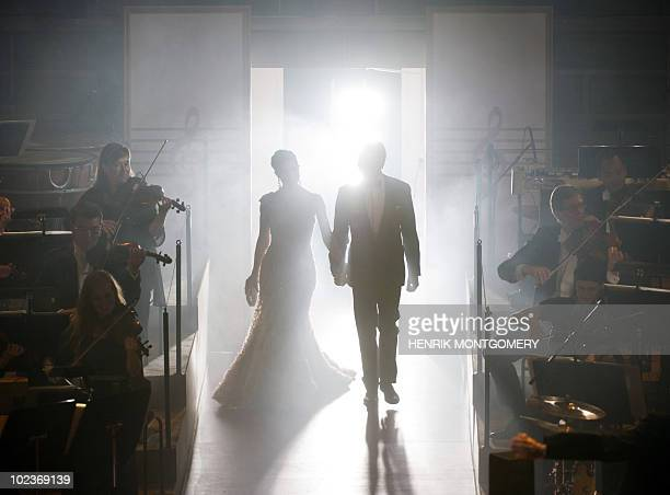 Sweden's Crown Princess Victoria and Daniel Westling walk on stage during a gala performance at the Stockholm Concert Hall in Stockholm on June 18 at...