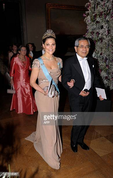 Sweden's Crown Princess Victoria walks with by Nobel Chemistry laureate Eiichi Negishi to the Prince's Gallery during the Nobel banquet in the...