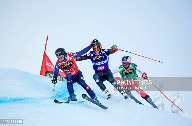 Sweden's David Mobaerg, Canada's Brady Leman and Switzerland's Ryan Regez compete during the 1/8th final heat of the men's Ski Cross final during the...