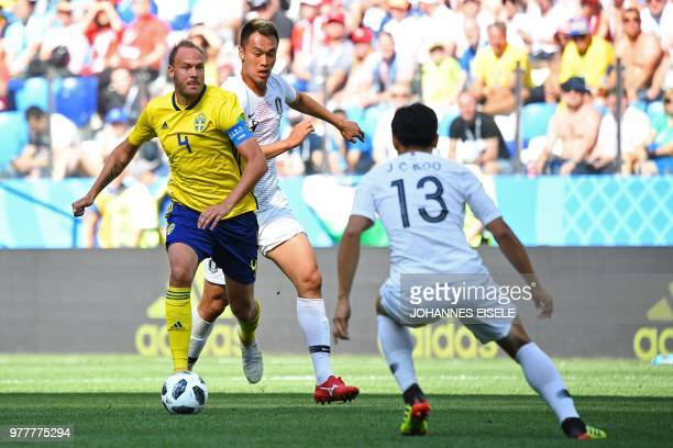 Sweden's defender Andreas Granqvist runs with the ball as he is mnarked by South Korea's forward Kim Shinwook and South Korea's midfielder Koo...