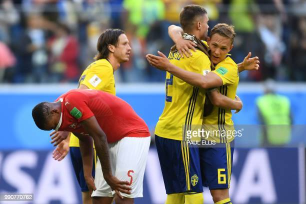 Sweden's defender Ludwig Augustinsson and Sweden's defender Mikael Lustig celebrate their victory past Switzerland's defender Manuel Akanji at the...