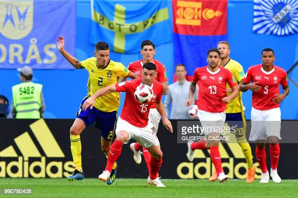 Sweden's defender Mikael Lustig and Switzerland's midfielder Blerim Dzemaili fight for the ball during the Russia 2018 World Cup round of 16 football...
