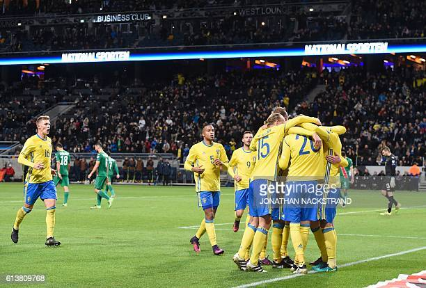Sweden's defender Victor Nilsson Lindelof celebartes with teammates after scoring during the WC 2018 football qualification match between Sweden and...