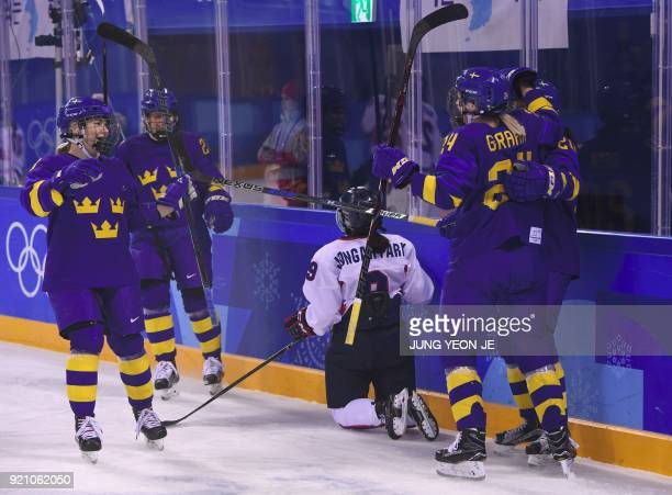 Sweden's Erika Grahm celebrates with teammates after a goal in the women's playoff classifications ice hockey match between the Unified Korea team...