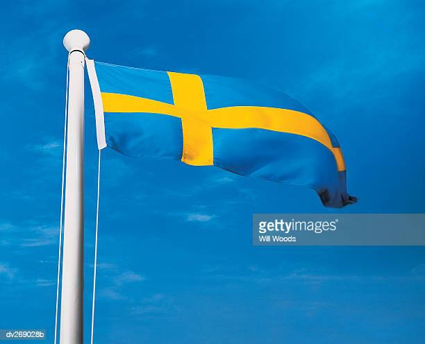 Sweden's flag on flagpole waving in wind