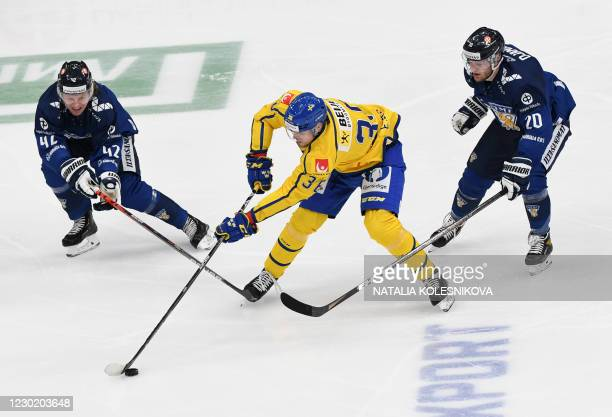 Sweden's forward Emil Larsson vies with Finland's Robin Salo and Finland's Niko Ojamaki during the Channel One Cup of the Euro Hockey Tour ice hockey...