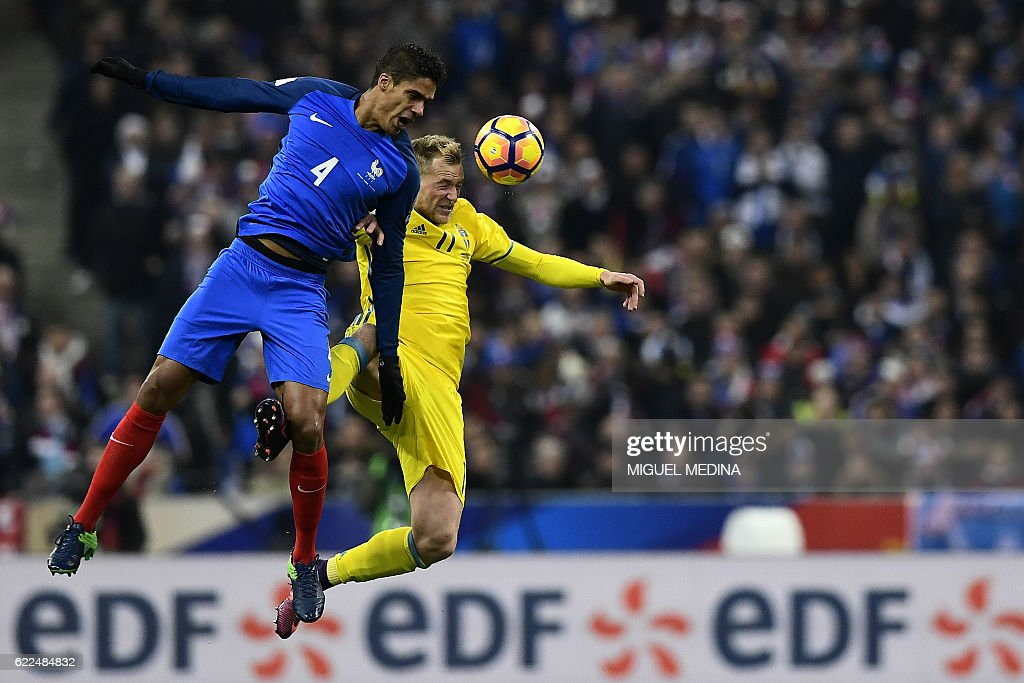 TOPSHOT - Sweden's forward John Guidetti (R) heads the ball with France's defender Raphael Varane during the 2018 World Cup group A qualifying football match between France and Sweden at the Stade de France in Saint-Denis, north of Paris, on November 11, 2016. / AFP / MIGUEL
