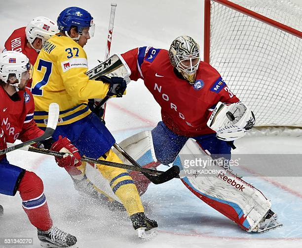 Sweden's forward John Norman attacks as Norway's goalie Lars Haugen saves his net during the group A preliminary round game Norway vs Sweden at the...
