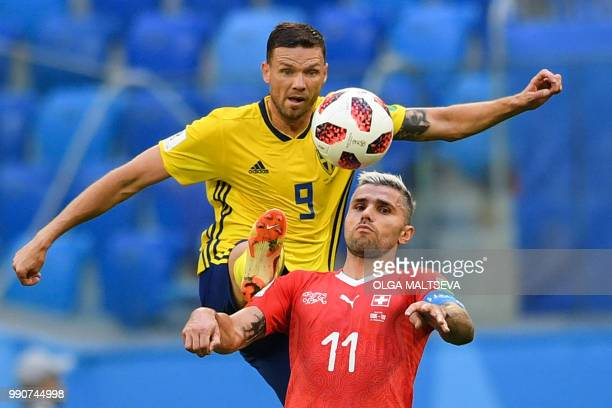 TOPSHOT Sweden's forward Marcus Berg fights for the ball with Switzerland's midfielder Valon Behrami during the Russia 2018 World Cup round of 16...
