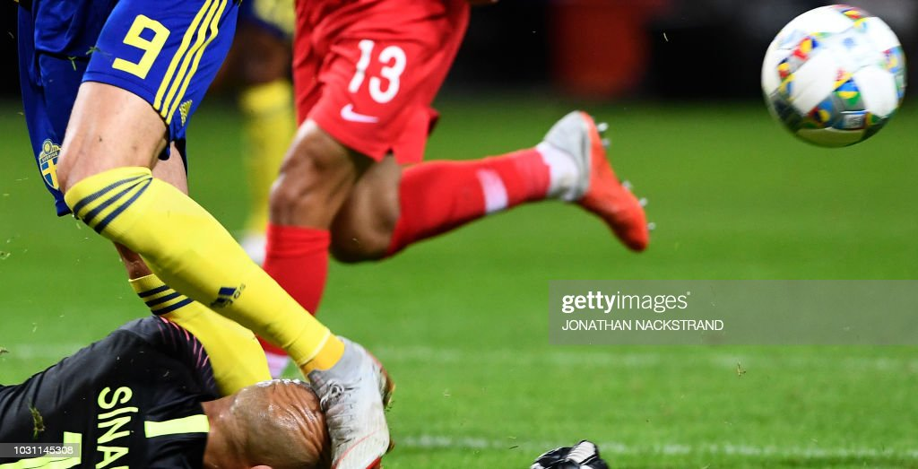 Sweden's forward Marcus Berg (L, no 9) hits Turkey's goalkeeper Sinan Bolat (bottom) during the UEFA Nations League football match between Sweden and Turkey at Friends Arena in Solna on September 10, 2018. (Photo by Jonathan NACKSTRAND / AFP) / ALTERNATIVE
