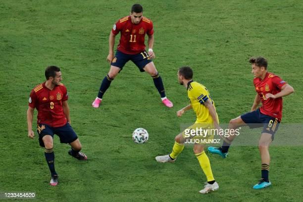 Sweden's forward Marcus Berg is marked by Spain's midfielder Marcos Llorente , Spain's midfielder Ferran Torres and Spain's midfielder Koke during...