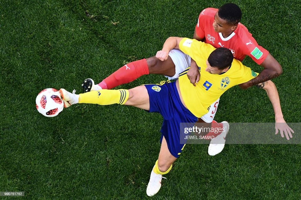 TOPSHOT - Sweden's forward Marcus Berg (L) vies with Switzerland's defender Manuel Akanji during the Russia 2018 World Cup round of 16 football match between Sweden and Switzerland at the Saint Petersburg Stadium in Saint Petersburg on July 3, 2018. (Photo by Jewel SAMAD / AFP) / RESTRICTED