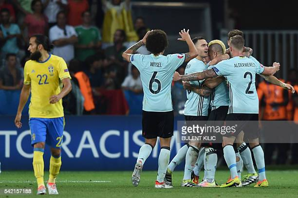 Sweden's forward Marcus Berg walks away as Belgium teamates celebrate the first goal of the match by Belgium's midfielder Radja Nainggolan during the...