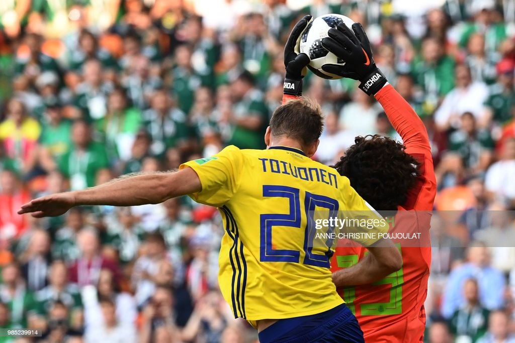TOPSHOT - Sweden's forward Ola Toivonen challenges Mexico's goalkeeper Guillermo Ochoa during the Russia 2018 World Cup Group F football match between Mexico and Sweden at the Ekaterinburg Arena in Ekaterinburg on June 27, 2018. (Photo by Anne-Christine POUJOULAT / AFP) / RESTRICTED
