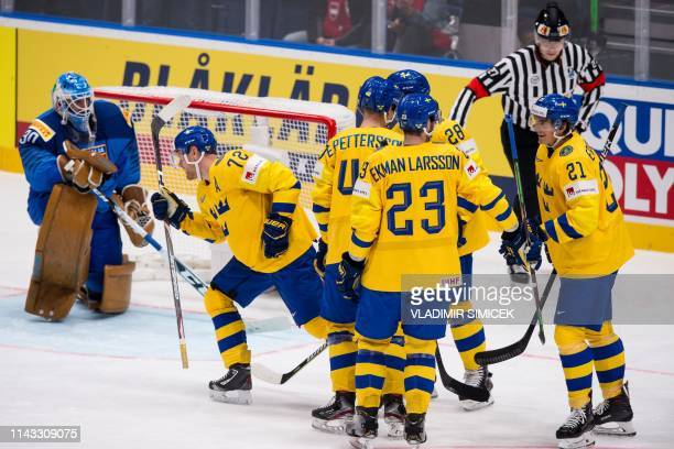 Sweden's forward Patric Hornqvist celebrates with teammates after scoring against Italy's goalkeeper Marco De Filippo Roia during the IIHF Men's Ice...