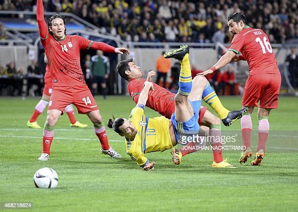 Sweden's forward Zlatan Ibrahimovic falls after shooting the ball between Iran's midfielder Andranik Teymourian defender Morteza Pouraliganji and...