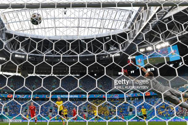 Sweden's goalkeeper Robin Olsen jumps and concedes Poland's first goal scores by Poland's forward Robert Lewandowski during the UEFA EURO 2020 Group...