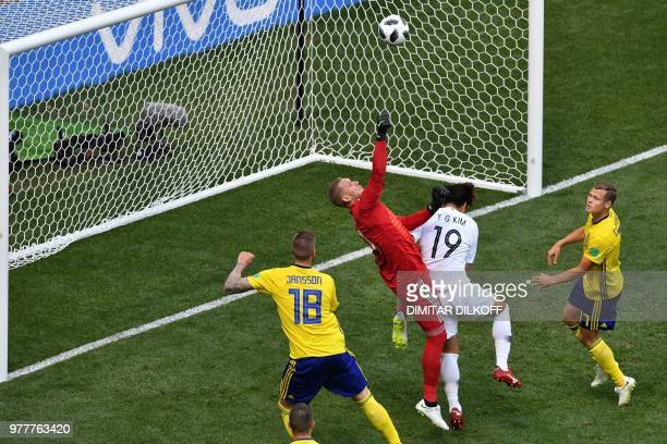 Sweden's goalkeeper Robin Olsen punches the ball ahead of South Korea's defender Kim Young-gwon during the Russia 2018 World Cup Group F football...