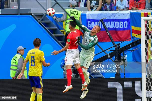 Sweden's goalkeeper Robin Olsen punches the ball away past Switzerland's midfielder Blerim Dzemaili as Sweden's midfielder Albin Ekdal looks on...