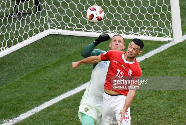Sweden's goalkeeper Robin Olsen vies with Switzerland's midfielder Blerim Dzemaili during the Russia 2018 World Cup round of 16 football match...