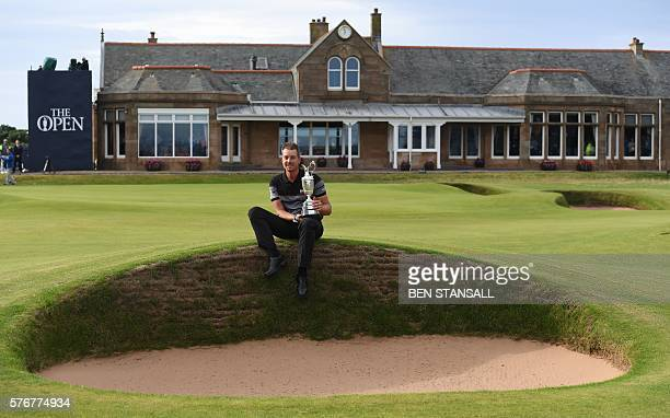 Sweden's Henrik Stenson poses for pictures in front of the clubhouse with the Claret Jug, the trophy for the Champion golfer of the year after...