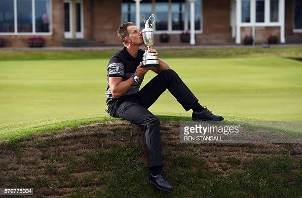 Sweden's Henrik Stenson poses for pictures in front of the clubhouse as he kisses the Claret Jug the trophy for the Champion golfer of the year after...