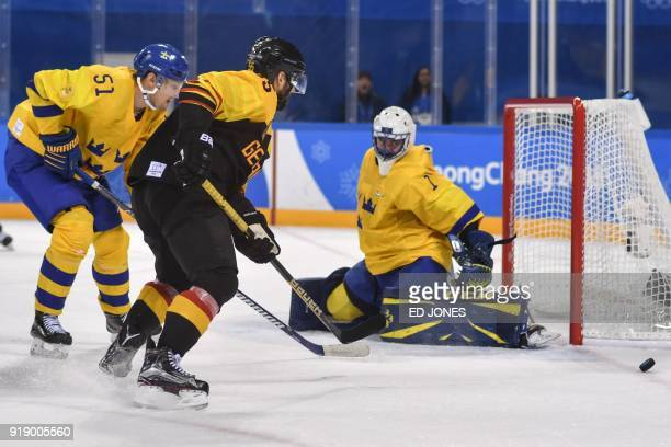 Sweden's Jhonas Enroth guards against a shot from Germany's Felix Schutz in the men's preliminary round ice hockey match between Sweden and Germany...