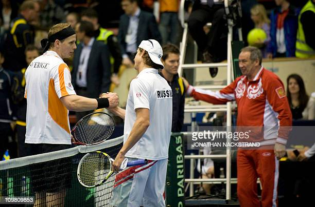 Sweden's Joachim Johansson and his captain Thomas Enqvist shake hands with Russia's Igor Andreev and his captain Shamil Tarpischev at the end of...