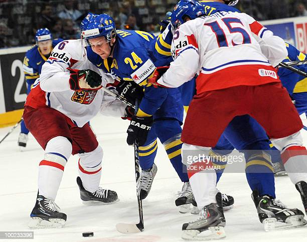 Sweden's Johan Harju tries to pass through Czech Tomas Mojzis Jakub and Jan Marek during the semifinal match between Sweden and Czech Republic during...