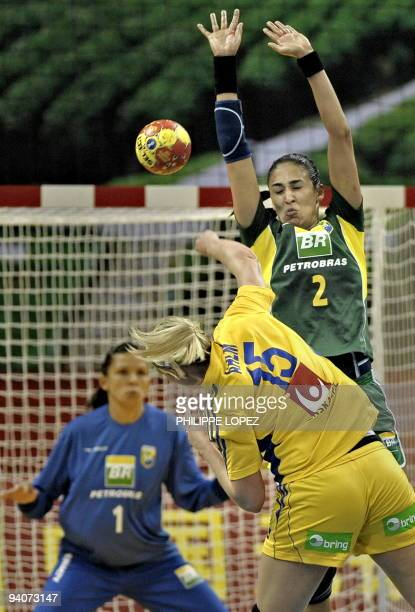 Sweden's Johanna Ahlm attempts to score as Brazil's Fabiana Diniz tries to block during the preliminary round match between Brazil and Sweden at the...