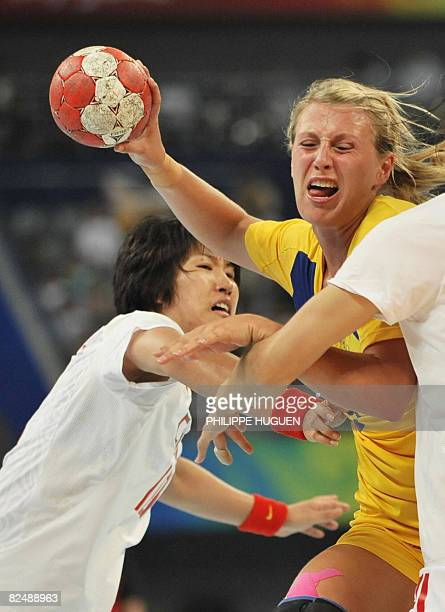 Sweden's Johanna Ahlm is marked by China's Wang Shasha during a women's placement 58 handball match of the 2008 Beijing Olympic Games on August 21...