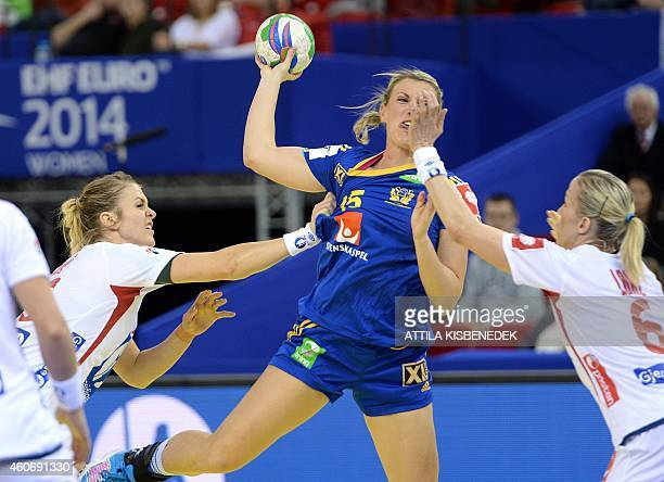 Sweden's Johanna Ahlm is pushed by Norway's Ida Alstad and Heidi Loke in Papp Laszlo Arena of Budapest on December 19 2014 during their semifinal...