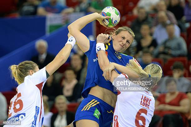 Sweden's Johanna Ahlm is pushed by Norway's Pernille Wibe and Heidi Loke in Papp Laszlo Arena of Budapest on December 19 2014 during their semifinal...