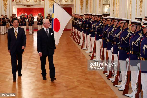 Sweden's King Carl XVI Gustaf and Japan's Prime Minister Shinzo Abe review a guard of honour during a welcoming ceremony at Akasaka Palace state...