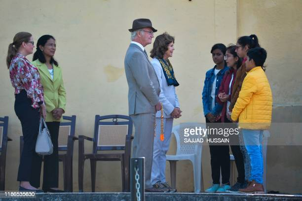 Sweden's King Carl XVI Gustaf and Queen Silvia attend speak with children as they arrive to attend a Ganga Arti Puja a prayer service on the banks of...