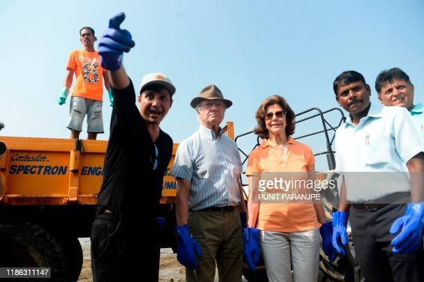 Sweden's King Carl XVI Gustaf and Queen Silvia listen to volunteers as they participate in a beach cleanup project a the Versova Beach in Mumbai on...