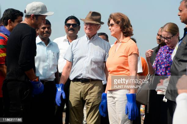 Sweden's King Carl XVI Gustaf and Queen Silvia listen to volunteers as they arrive to participate in a beach cleanup project a the Versova Beach in...