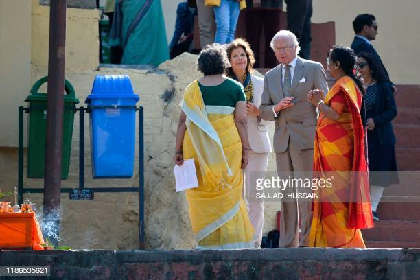 Sweden's King Carl XVI Gustaf and Queen Silvia speak with two female priests as they arrive to attend attend a Ganga Arti Puja a prayer service on...