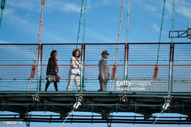 Sweden's King Carl XVI Gustaf and Queen Silvia walk on the Ram Jhula bridge over Ganga river in Rishikesh on December 5 2019