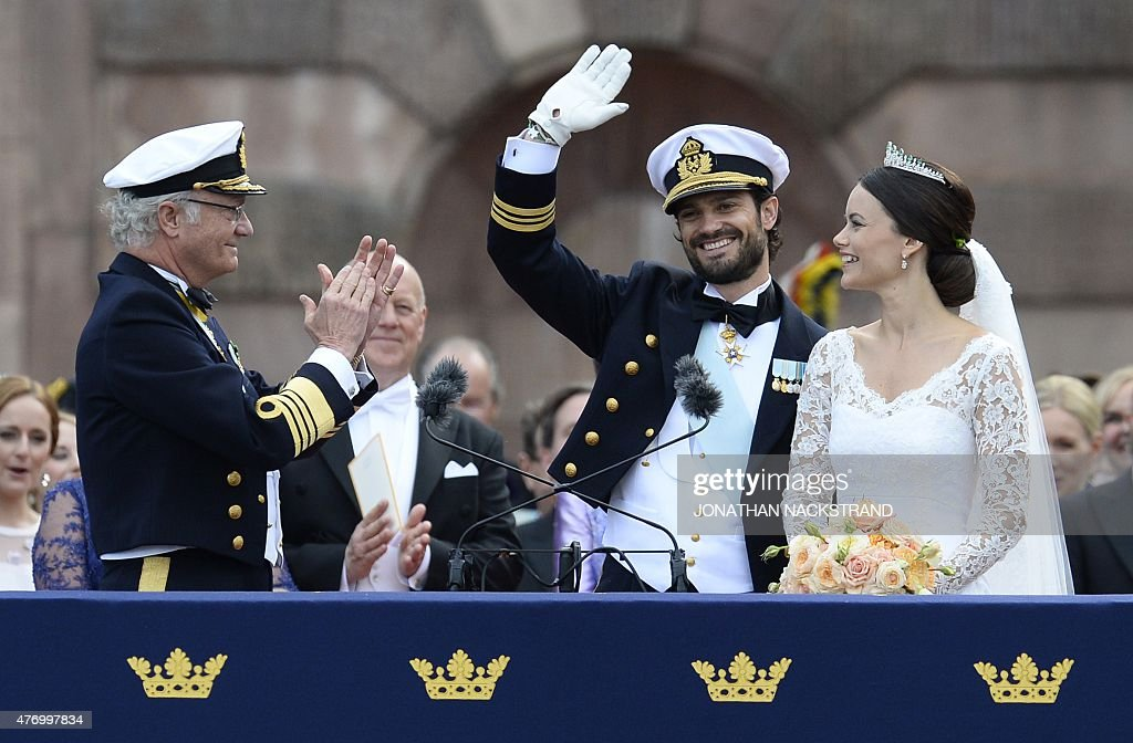 Sweden's King Carl XVI Gustaf (L) applauds the newly wed couple Sweden's Princess Sofia (R) and Sweden's Prince Carl Philip after their wedding ceremony at Stockholm Palace on June 13, 2015.