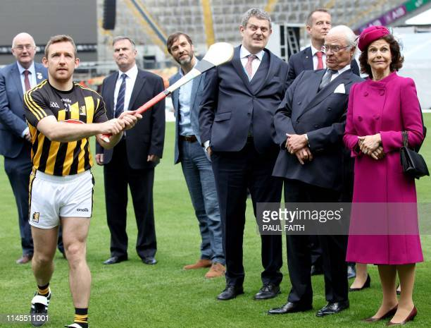 Sweden's King Carl XVI Gustaf reacts as he and his wife Queen Silvia watch a hurling demostration at Croke Park, the home of the Gaelic Athletic...