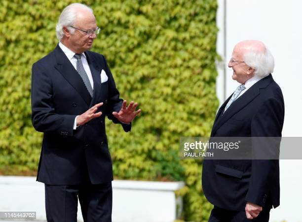 Sweden's King Carl XVI Gustaf reacts as he talks with Ireland's President Michael D Higgins after arriving at Pheonix Park in Dublin on May 22 on the...