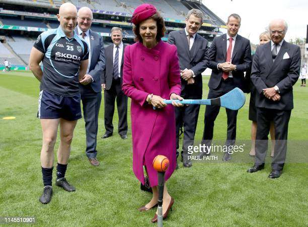 Sweden's King Carl XVI Gustaf watches as his wife Queen Silvia tries her hand at hurling, at Croke Park, the home of the Gaelic Athletic Association...