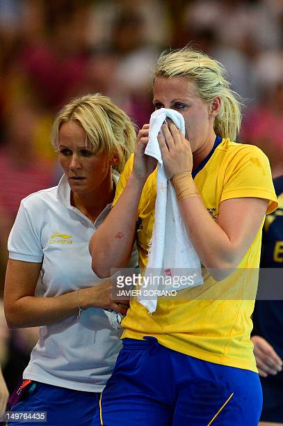 Sweden's leftback Johanna Ahlm puts a towel on her face after being injured during the women's preliminary Group B handball match Spain vs Sweden for...