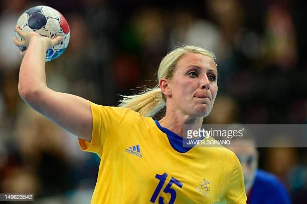 Sweden's leftback Johanna Ahlm sticks out her tongue as she prepares to shoot during the women's preliminaries Group A handball match France vs...