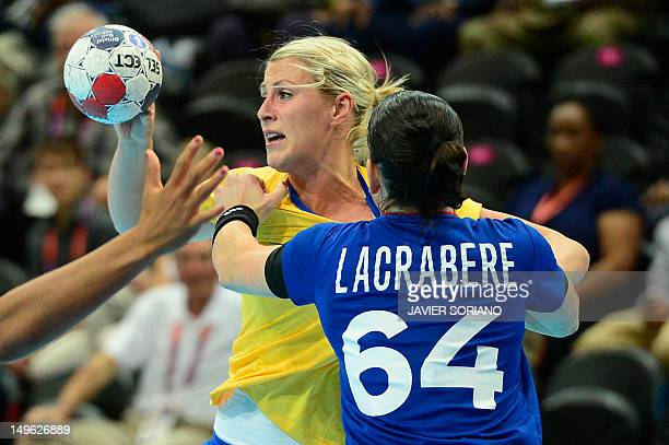 Sweden's leftback Johanna Ahlm vies with a french player during the women's preliminaries Group A handball match France vs Sweden for the London 2012...