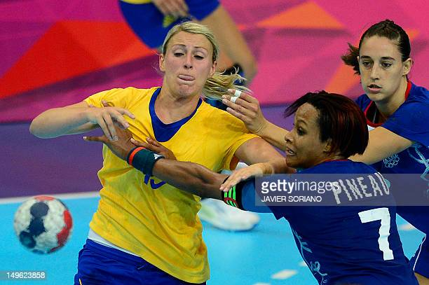 Sweden's leftback Johanna Ahlm vies with France's centreback Allison Pineau during the women's preliminaries Group A handball match France vs Sweden...