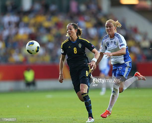 Sweden's Lotta Sjolin is chased by Finland's Anna Westerlund during the UEFA Women's EURO 2013 group A football match between Finland and Sweden at...