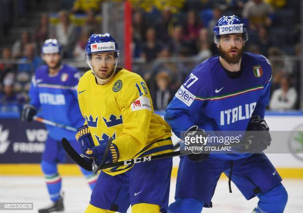 Sweden's Marcus Kruger and Italy's Thomas Larkin vie during the IIHF Ice Hockey World Championships first round match between Sweden and Latvia in...